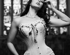 For the romantic at heart, this alluring custom handmade lace corset wedding dress is the epitome of style and elegance. It will be custom tailored to hug all of your curves in perfect detail and will enhance your bust line magnificently. It features a steel boned corset top that cascades into a billowing lace skirt. The effect is romantic and seductive. It reveals just the right amount of skin to keep things interesting while providing maximum coverage for the blushing bride. A full corset…
