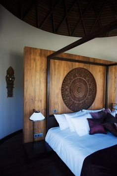 Bedrom in a villa in Bali. Love the contrast of dark and light wood on the wall. The traditional dark wood wall plaque creates an instant visual impact against the crisp white sheets. The dark wood ceiling is tied in so well with the bed and dark cushions. A gorgeous bedroom.