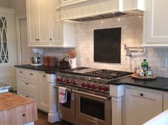 Antique fireback as backsplash by https://www.firebacks.net