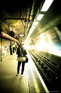 Photographer Eugene Nikiforov took this photograph of people waiting for a train. I like this photo because it contains a variety of yellow colour tones and lens flare due to the artificial lighting. The photo also follows the rule of thirds by placing the woman along the first vertical and the track along the second vertical.