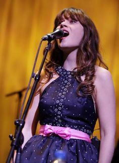 Black dot print dress with pink bow belt at She & Him concert in Grand Prairie, TX