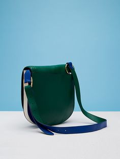 This crescent shaped saddlebag has contrast piping detail, a gold tone ring detail, and an adjustable shoulder strap for hands-free crossbody wear. Featuring a flap closure, and pops of contrasting colors throughout, this bag has a compact shape, yet is roomy enough to fit all your essentials and more.