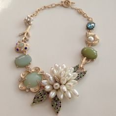 Amazing Gorgeous Summer theme statement necklace Approx 19 inches long, beautiful matte gold color finish, with amazing charm adornments. Statement, eye candy, necklace. Has coral shaped charms, 1 w/ white crystals, charms w/ crystal inlays & faux pearl center, bezeled, multiple light green colors, from sea foam, sage & darker. Aqua marine Crystal that reflects light beautifully. Amazing center piece with Pearl colored elongated beads forming a flower with ✨ Sparkling Crystal inlaid into…
