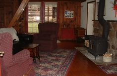 The Tree House's spacious living room has two sets of French doors, one toward the Log Cottage and one looking toward the deck and creek. Please note the stairway on left. It is steep but safe with multiple hand-holds. Creekview Country Cottage Bed and Breakfast in Muncy, Pennsylvania