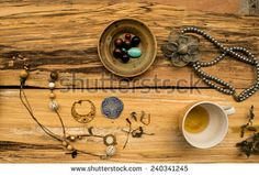 Old table with cup of tea, necklace and perls - stock photo