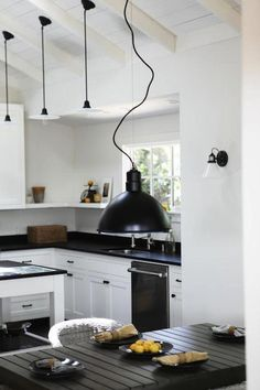 The kitchen counters are honed black granite with a textured leather finish (not super-shiny). Love the white cabinets, dark pulls, dark counters with not super dark floor.