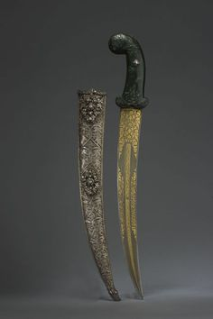 """Jade-hilted Dagger with gold-inlaid inscribed blade & diamond-set silver scabbard.  Medium: Ottoman  Location: Turkey  Dated: circa 18th century  Inscriptions: The inscriptions include two couplets in Turkish and the Arabic: """"There is no youth [as brave as] 'Ali, no sword [as sharp as] dhi'l-faqar"""".  The watered steel blade with a double band of inscription on either side, floral interlace on the forte, the spinach jade hilt carved with irises and with an appliqué rose-diamond roset."""
