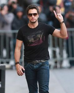 """Luke Bryan is all rock here. We aren't just talking about his rocker T-shirt or his """"rock on"""" hand symbol or even his rocker 'tude. Actually, we're mostly talking about the rock-hard muscles under the T-shirt"""