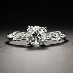 Hand-fabricated in platinum, circa 1920s-30s, this elegantly understated and artfully stylized take on a traditional solitaire shines front and center with a bright white and sparkling European-cut diamond, weighing .78 carat. The beautiful stone scintillates between glittering tapered bow motif ribbons leading to a sleek knife-edge ring shank. A timeless, original Art Deco sparkler. Currently ring size 6.