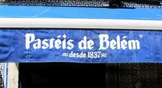 """Bue and white sign of the Pastéis de Belém bakery with the date, """"since 1837"""""""
