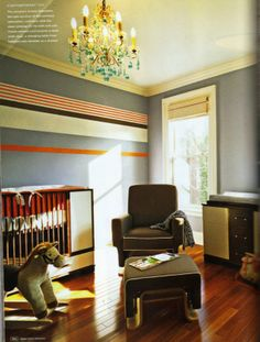 boy's nursery thanks to elements of style. slate gray and orange horizontal striped walls, crystal chandelier, modern crib and brown glider and ottoman.