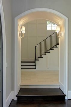 Arched entry , trim , flooring , staircase & railing . Love the mix of light & dark .