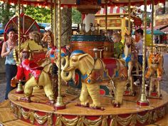 An adorable little carousel, apparently Victorian era, with a monkey, an elephant, and a tiger, in addition to horses.