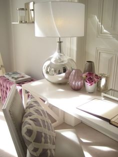 Stunning office guest bedroom design with gray walls paint color, white desk, mercury glass lamp, white French chair upholstered in gray leather with silver nailhead trim, white & purple lattice pillow, gray & plum glass vases and plum velvet tufted ottoman.