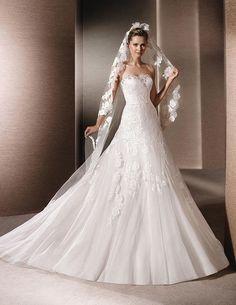 Romántico traje de color blanco con encaje, escote corazón, cintura ceñida, y falda amplia con tul. Ten en cuenta que combina muy bien con velo de encaje. Perfecto para una novia romántica y delicada que contraerá matrimonio en otoño.