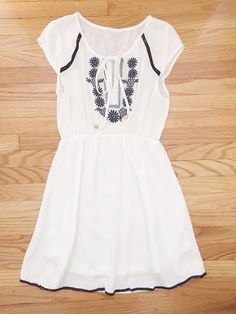 """Feminine white dress features an elegant embroidered neckline with a slightly gathered waist and cap sleeves. Slip on dress is lined from the waist down. Cotton. Imported. Length: 35"""""""