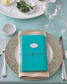 Passover Place Setting - If you plan to ask guests to read from the Haggadah, consider incorporating the book of prayers and stories into every setting. We covered each book in a sheet of decorative paper and a layer of blue vellum to coordinate with the dishes. Then we used silk cord to bundle it with the napkin. Self-adhesive labels let the books double as place cards.