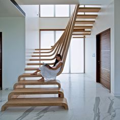Waves of wood form staircase at SDM Apartment by Arquitectura en Movimiento Workshop