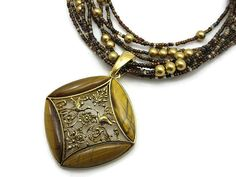 A vintage multi strand beaded necklace, with a large tiger eye pendant. By Joan Rivers. The pendant is removable from the necklace.  Necklace
