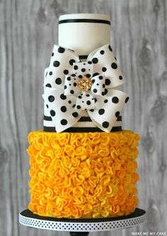 A black and white cake with a bold pop of yellow. Featuring stripes, polka dots, ruffles and an incredible oversized bow. Created by Make Me My Cake.