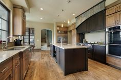 Large kitchen integrating two tones of wood.  One set of custom cabinets is topped with tile.  Flooring is hard wood.  There are two main work space, each with a sink.