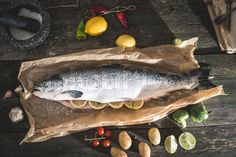 Stock image of 'Preparing whole salmon fish for cooking. Vegetables on the table. Vintage style'