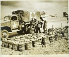 """Marmite containers with blood for the European Theater of Operations (marked """"ETO"""") are being sorted at a military airfield in France, 1944. 400 to 500 bottles of blood were collected daily by the blood bank at the 152d Station Hospital at Salisbury, England (the base of the ETOUSA blood bank) and flown to the EOT in iced marmite cans. These cans held sufficient wet ice to maintain desired temperatures for 24 hours or more."""