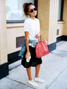 A white t-shirt is worn with a black skirt, tennis shoes, red tote bag and a denim jacket tied at the waist.