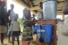 Girl washing her hands using handwashing equipment provided by Plan