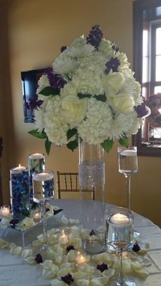 Arrangement of white hydrangea, white Polar Star roses, purple stock, and white spider mums atop a clear cylinder with a diamond band.