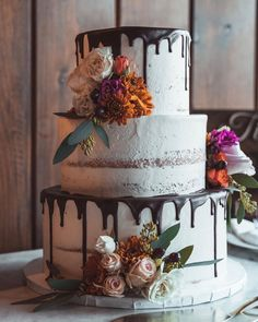 Three tiers of rustic goodness. From the drippy chocolate to the naked case base to the fresh florals, this is one of our favorite rustic wedding cake ideas. See more rustic wedding cake, decor, and dress ideas at rusticweddingchic.com 📸: @dawnpointstudios 🍰: @theluckycupcakecompany Wedding Cake Base, Wedding Cake Rustic, Wedding Cake Designs, Chocolate Drip Cake, Two Tier Cake, Wedding Cake Inspiration, Wedding Ideas, Wedding Cakes With Cupcakes, Take The Cake