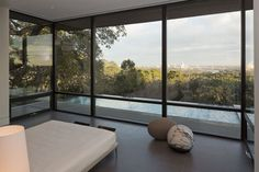 This bedroom with floor-to-ceiling windows, enjoys the views of downtown Austin and the pool outside.