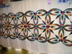 This quilt, bed runner, table runner?  I am not quite sure what it is but love the play the quilter took on the double wedding ring quilt block.  I love the star points she incorporated into her design.  This quilt was displayed at the Long Islanders Quilters Society quilt show.