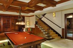 Game room with orange pool table, vaulted ceilings, and bay window seat.