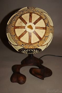 https://flic.kr/p/jDjBPX | Table lamp IX | Head of the lamp is made of Senegalese calabash. White parts are carved layer of the fruit which change the color to red/orange when the lamp is switched on. On the bottom of the lamp there's perforated closing part locked by magnets. The lamp was painted with wood oil and alcohol ink. Black parts are burnt calabash surface. The center element is genuine Baltic amber- ranked as the world's finest;  resin from the ancient trees dating back ~40…