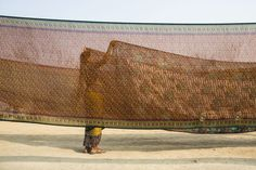 A Hindu devotee holds out a sari to dry after having bathed on the banks of the Ganges river on January 13, 2013 in Allahabad, India. (Daniel Berehulak/Getty Images)