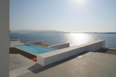 React Architects designed two summer homes in Paros that adapt to their surrounding environment and Cycladic architecture features, overlooking the sea and neighboring island of Antiparos.