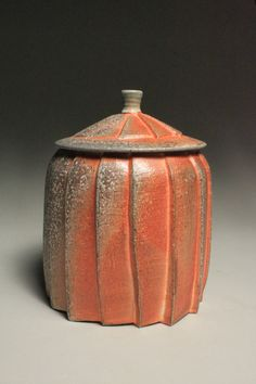 This jar was thrown on the potter's wheel and hand carved. It was fired in a soda kiln to cone 10 with a food safe yellow celadon on the inside and flashing slip on the exterior. It is a good size jar to store cookies, pasta, or cherished belongs.