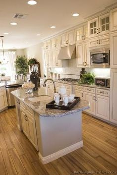 I like the side counter with dishwasher placement. functional and cute... antique white kitchen cabinets with light grey and white granite but I would do dark laminate wood floors. I am not of fan of that color for wood floors by alambra