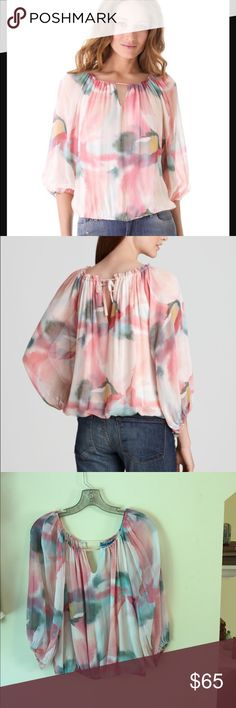 Alice & Olivia Silk Watercolor Keyhole Blouse This gorgeous silk blouse is a watercolor print of soft pastels. There is a keyhole front and back and the neckline is stretchy enough that i think it could even be worn off the shoulders. Center is lined and the sleeves are sheer. No stains or snags. The only thing that shows it may have been worn is a small A written on the tag! New, this top retails for $295! Alice & Olivia Tops Blouses