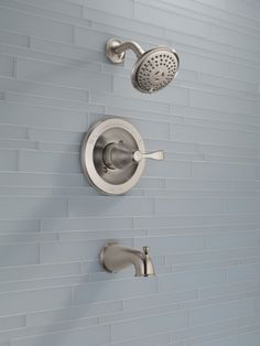 Pale blue bathroom tile pairs well with a brushed nickel shower head from the Delta Faucet Porter collection.