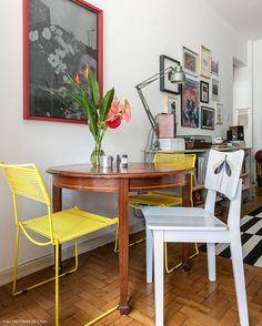 Mesa de madeira antiga misturada com cadeiras de desenho mais moderno.