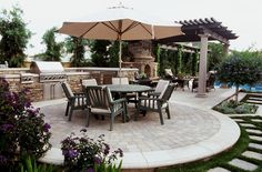 Pretty patio kitchen / outdoor living design with a nice circular dining area set on textured concrete. Love the pretty small flowering tree ( a purple crape myrtle??)