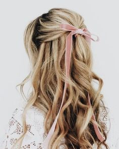 Simple half up hair with curls and a pink velvet bow.