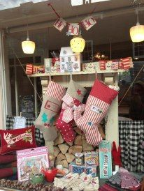 Create a cozy atmosphere in your shop by simulating a fireplace with stuffed stockings with your merchandise and wrapped packages.