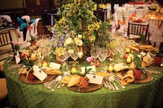 A very tropical wedding tablescape! Recreate with an olive green pintuck linen, gold chargers, and yellow napkins. A pretty tropical centerpiece is a must!