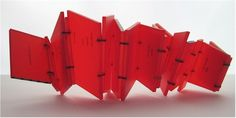 Construction, 2010 Plexi-Glass, Vellum, inkjet printed, 15 x 3.5 x .5 inches, fully open. A small red irregular shaped book, which sits as a stack of odd sized pages bound together in an uneven fashion, opens slowly, crankily and pulls up to reveal a poem printed on luminescent blockish pages