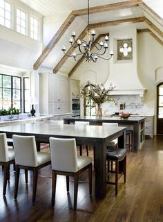 In the kitchen, the islands are covered in Imperial Grey marble. The A. Rudin stools are upholstered in Breaker by DeLany & Long. The Clinton chandelier is by Paul Ferrante.