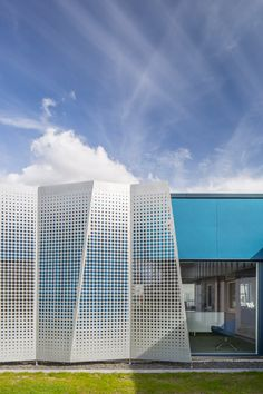 Sheets of perforated metal were used to create a faceted facade for this office extension.