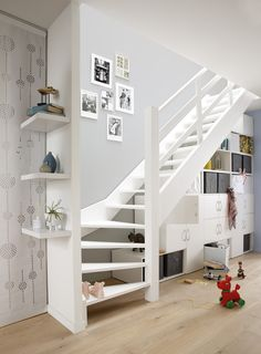 White stairs with gallery wall and bookshelves